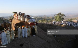 "LALIBELA, ETHIOPIA - JANUARY 08:  Priest and deacons pause during a processional around Beta Mariam Church on January 8, 2016 in Lalibela, Ethiopia.   Amoungst the numerous icons and crosses the priest carry the original Afro Aygebam or ""Lalibela Cross"" which dates back to the twelthf century during the rule of King Lalibela.  Thousands of adhearants to the Ethiopian Orthodox Faith descend upon the Ethiopian city of Lalibela to observe Orthodox Christmas which this year takes place January 6th, 7th and 8th of 2016.  Christmas or Gena as it is known in the Amharic tongue usually takes place on January 7 and is observed throughout the Orthodox communities of the world but the celebrations held in Ethiopia this year span 3 days due to a leap year in the Ethiopian calender.  The city of Lalibela is home to 11 rock hewn churches constructed by Ethiopian King Lalibela during the course of his rule in the twelfth and thirteenth centuries and are deemed amoung the seven man made wonders of the world.  Some of those that make the pilgramage to Lalibela come from all over Ethiopia and all over the world with some pilgrims in attendance having walked 3 weeks to attend the celebrations.  (Photo by J. Countess/Getty Images)"
