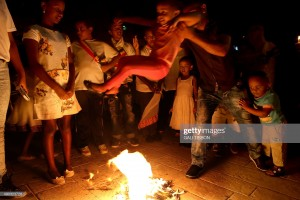 A member of the Ethiopian church swings his child over flames for a blessing as they celebrate 'Meskel', the feast of the Exaltation of the Holy Cross, at the Ethiopian monastery on the roof of the Church of the Holy Sepulchre in Jerusalem's Old City on September 27, 2015. Meskel, Ge'ez word for cross, is an annual celebration that commemorates the finding of the 'True Cross' by the Queen Helena mother of Constantine the Great in the fourth century. AFP PHOTO / GALI TIBBON        (Photo credit should read GALI TIBBON/AFP/Getty Images)